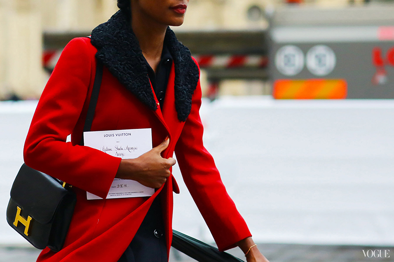 Shala Monroque in a red coat at Paris Fashion Week photographed by Phil Oh for Vogue