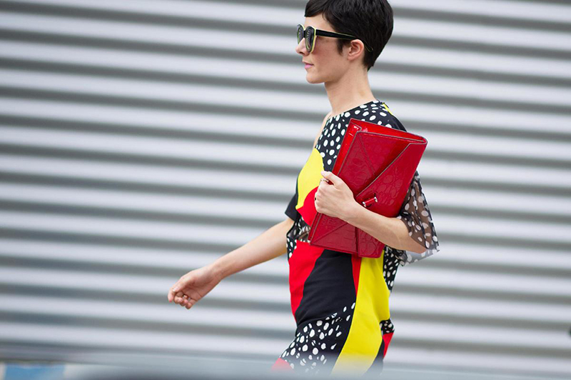 Violaine Bernard matching her red clutch to her multi coloured outfit