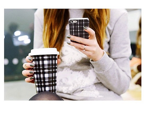 London blogger Julia Shutenko in the Even Deeper Jumper while hanging out at London Fashion Week with her tartan print iPhone cover and coffee cup by Finders Keepers